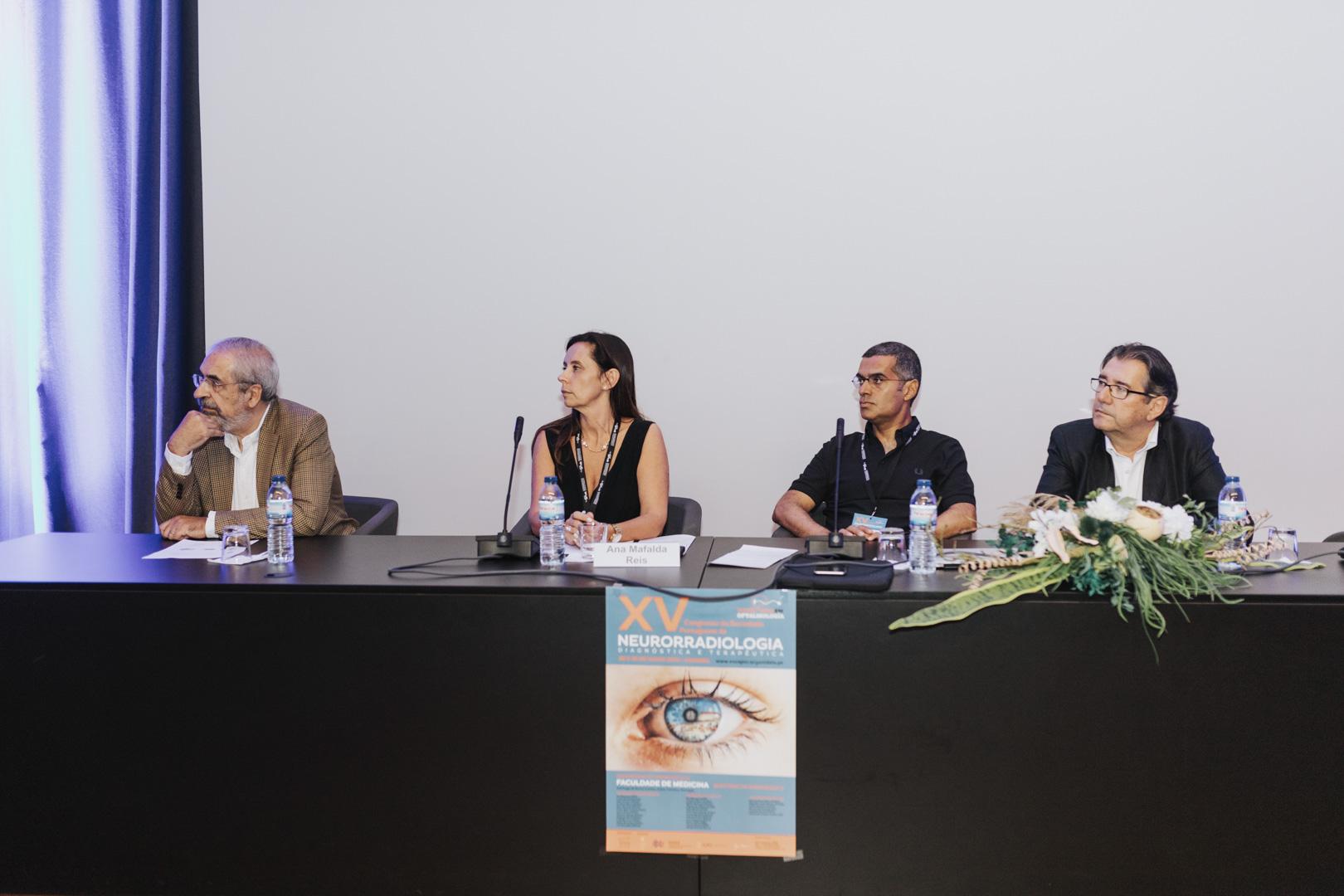 XV Congresso da SPNR - Moderadores na Mesa Presidencial durante as sessões, com o cartaz do Congresso